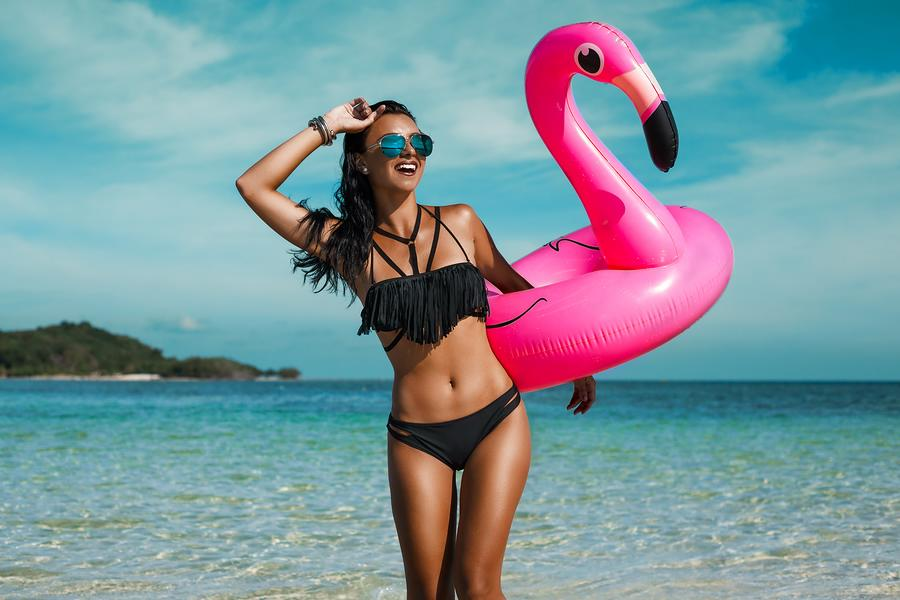 A photo of a happy woman on the beach, carrying a large flamingo pool float.