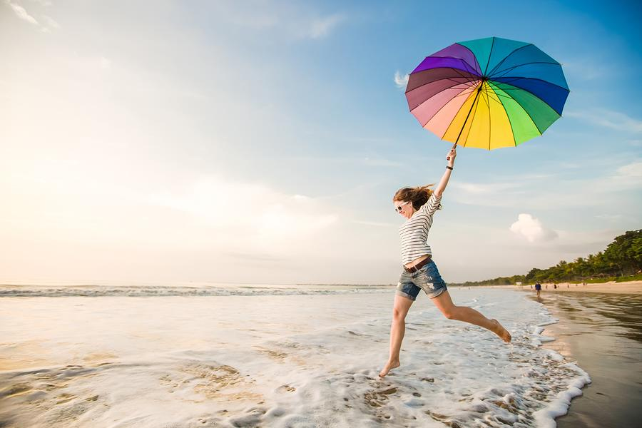 A photo of a happy woman carrying a colorful umbrella, splashing through foamy waves on the beach.