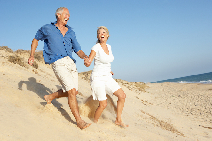 A photo of a happy, mature couple running across sand dunes by the ocean.